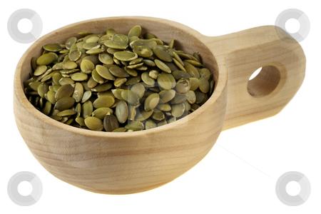 Roasted pumpkin seeds stock photo, Roasted pumpkin seeds (pepita) in a rustic wood cup (scoop),  isolated on white by Marek Uliasz