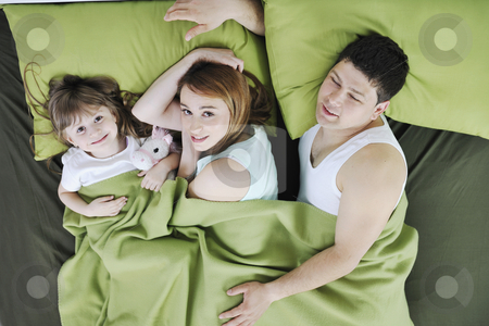 Happy family relaxing in bed stock photo, Happy young family relaxing in bed by Benis Arapovic