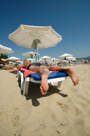 Relaxation in the sun stock photo, People lying on sunbeds. Taken on a sunny day. by Lars Christensen