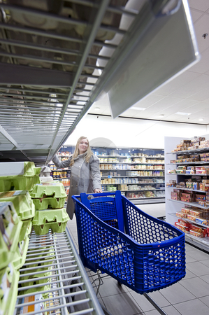 Supermarket stock photo, Woman with a cart shopping in a supermarket by Corepics VOF