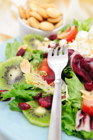Salad With Feta Cheese stock photo, Mediterranean style salad with different types of lettuce, tomatoes, slice kiwi fruit and almonds and a small bowl of oyster crackers. by Lynn Bendickson
