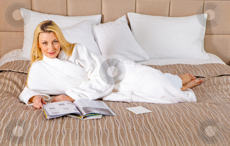 Woman Lying on Bed reading magazine stock photo, An attractive woman in a bathrobe lies on a bed. Reading magazine. Horizontal shot. by Ruta Balciunaite