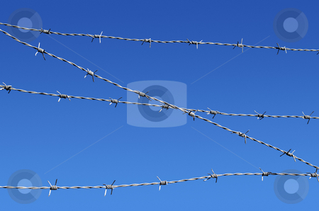 Barbed wire security fence close up and blue sky. stock photo, Barbed wire security fence close up and blue sky. by Stephen Rees