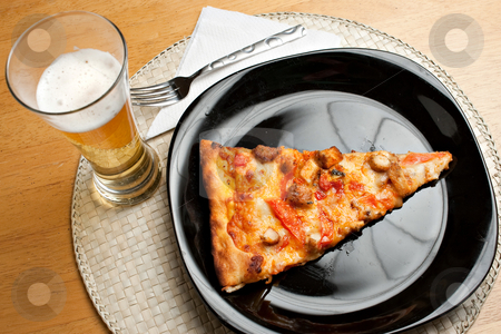 Pizza and Beer stock photo, A single slice of buffalo chicken pizza and a glass of golden lager beer.  The perfect weekend take out dinner. by Todd Arena