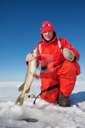 Ice fisherman stock photo, Happy ice fisherman holding a northern pike by Steve Mcsweeny