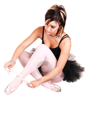 A young ballerina tying her ballet slippers. stock photo, An very pretty young ballerina sitting on the floor in the studio and tying her ballet slippers in a black twill dress and white pantyhose, for white background. by Horst Petzold