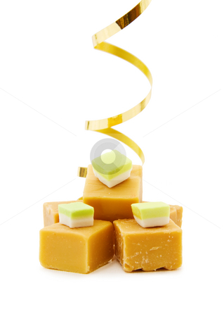 Caramel fudge blocks stock photo, Joy of food - caramel fudge with golden ribbon. Isolated on white background. by Andreea Chiper
