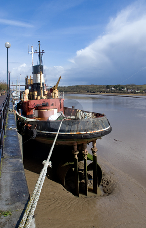 Tug Boat At Low Tide stock photo, Tug boat moored at low tide by Paul Phillips