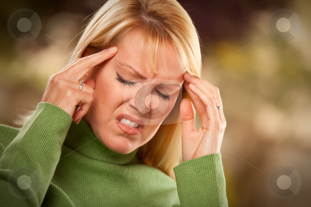 Grimacing Woman Suffering a Headache stock photo, Grimacing Woman Suffering a Painful Headache. by Andy Dean