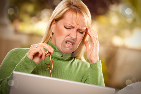 Grimacing Woman Using laptop Suffering a Headache stock photo, Grimacing Woman with Glasses Using Laptop Suffering a Painful Headache. by Andy Dean