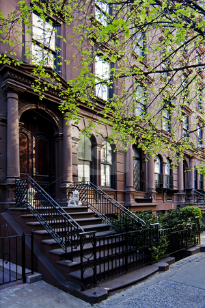 Brownstone townhouse stock photo, A residential New York, Philadelphia, Boston or Chicago brownstone townhouse building with balck fence and steps in front. by Paul Hakimata