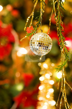 Cristmas disco ball bauble stock photo, Celebrating the magic of Christmas night with sparkling disco ball decoration and golden lights tree. by Andreea Chiper