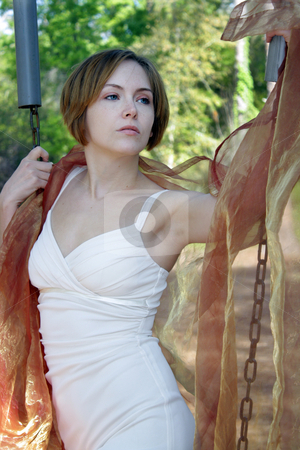 Beautiful Young Woman Outdoors (10) stock photo, A lovely young woman soaks up the morning sun outdoors with some sheer fabric. by Carl Stewart