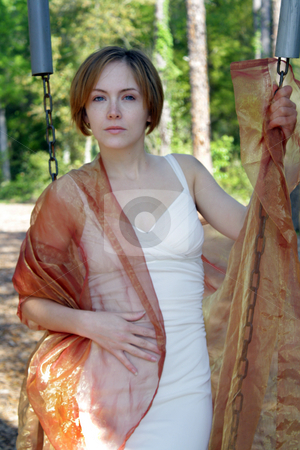 Beautiful Young Woman Outdoors (11) stock photo, A lovely young woman soaks up the morning sun outdoors with some sheer fabric. by Carl Stewart