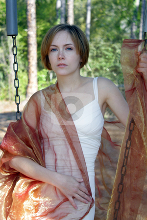 Beautiful Young Woman Outdoors (12) stock photo, A lovely young woman soaks up the morning sun outdoors with some sheer fabric. by Carl Stewart