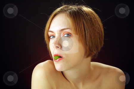 Beautiful Young Woman with Candy (1) stock photo, A lovely young woman holds a piece of hard candy in her lips. by Carl Stewart
