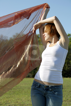Beautiful Young Woman Outdoors (3) stock photo, A lovely young woman soaks up the morning sun outdoors with some sheer fabric. by Carl Stewart