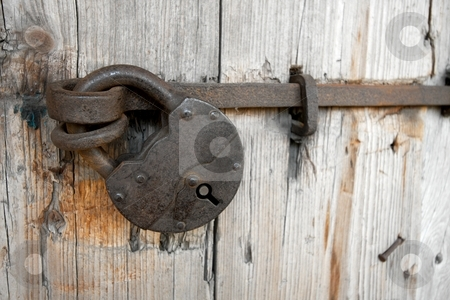 Padlock stock photo, Old padlock on a wooden door by P?