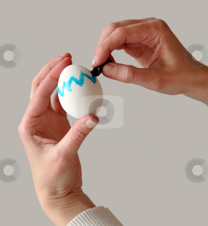Coloring easter egg stock photo, Female hands coloring an easter egg with gray background that is easy to remove by Frank G?