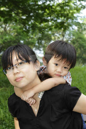 Piggyback ride stock photo, An Asian mother giving her son a  piggyback ride in a public park by Adrin Shamsudin
