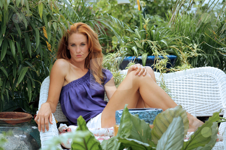 Beautiful Redhead in a Garden (9) stock photo, A lovely young redhead sits on outdoor furniture in a lush, cultivated garden. by Carl Stewart