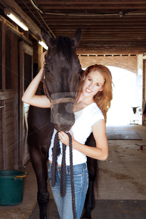 Beautiful Redhead with Her Horse (2) stock photo, A lovely young redhead with her horse inside the barn. by Carl Stewart