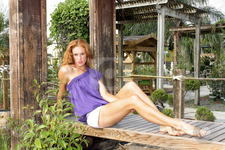 Beautiful Redhead in a Garden (3) stock photo, A lovely young redhead sits on a wooden rack in a lush, cultivated garden. by Carl Stewart