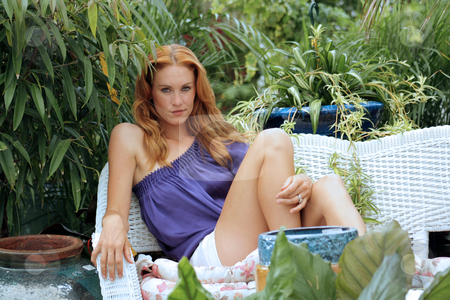 Beautiful Redhead in a Garden (7) stock photo, A lovely young redhead sits on outdoor furniture in a lush, cultivated garden. by Carl Stewart