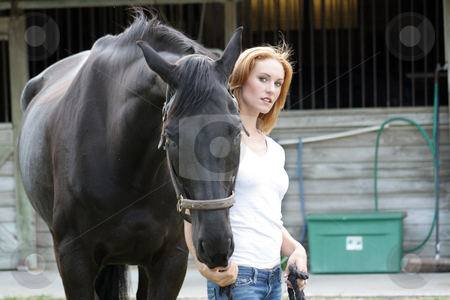 Beautiful Redhead with Her Horse (7) stock photo, A lovely young redhead with her horse in front of the barn. by Carl Stewart