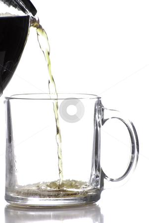 Pouring Coffee stock photo, Coffee being poured into a clear coffee cup, shot against a white background by Richard Nelson