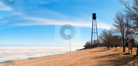 Spring Beach stock photo, A rural beach in the spring with the lake still frozen, shot with a blue sky by Richard Nelson