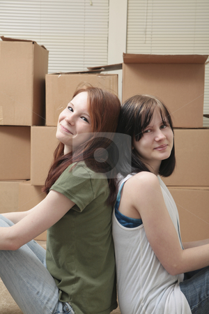 Teen sisters moving stock photo, Two teenage sisters sit back to back while taking a break from moving by Christy Thompson