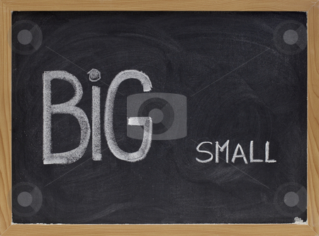 Big and small - opposite or contrast concept stock photo, Words big and small handwritten with white chalk on blackboard, contrast, opposiiton or contradiction concept by Marek Uliasz
