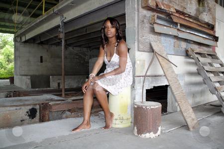 Beautifuy Black Woman at Abandoned Warehouse (23) stock photo, A lovely young black woman sits amidst the clutter of a long-abandoned warehouse. by Carl Stewart