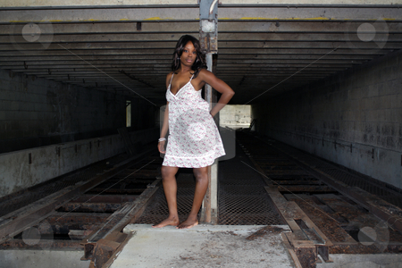 Beautifuy Black Woman at Abandoned Warehouse (24) stock photo, A lovely young black woman stands in front of a rail at a long-abandoned warehouse and loading facility. by Carl Stewart