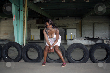 Beautifuy Black Woman at Abandoned Warehouse (25) stock photo, A lovely young black woman sits on old automobile tires at a long-abandoned warehouse and loading facility. by Carl Stewart