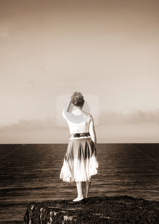 Woman looking at the sea stock photo, Woman with blonde hair looking at the sea. Custom black and white with sepia tinting. by Andreea Chiper