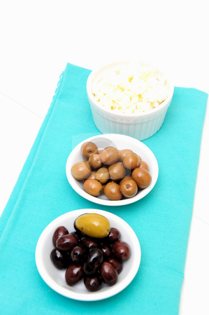 Olive Green And Black stock photo, Green and black marinated olives and feta cheese in small white bowls on a blue napkin by Lynn Bendickson