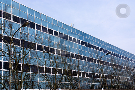 Glass building stock photo, Front of an office buildung with many windows. Modern design by Paul Phillips