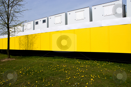 Row of construction buildings stock photo, Temporary site buildings for a construction staff, behind a bright yellow security fence by Paul Phillips