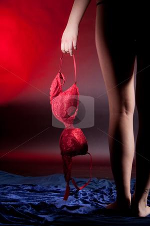 Woman holding a red bra stock photo, Silhouette of woman legs and hand holding a red bra by Ruta Balciunaite