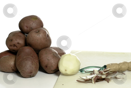 Peeling Potatoes stock photo, Peeled and unpeeled potatoes shot on a cutting board, isolated against a white background. by Richard Nelson