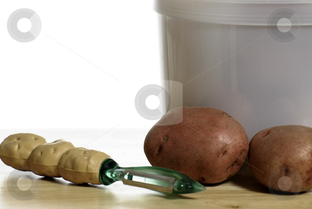 Peeling Potatoes stock photo, A potato peeler and organic red potatoes shot on a wooden table with a white background by Richard Nelson