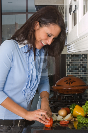Cutting vegetables stock photo, Young woman cutting vegetables in the kitchen by Anneke