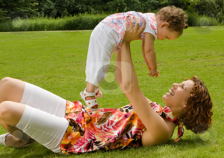 My little girl stock photo, Loving mother holding her little girl in the park by Anneke