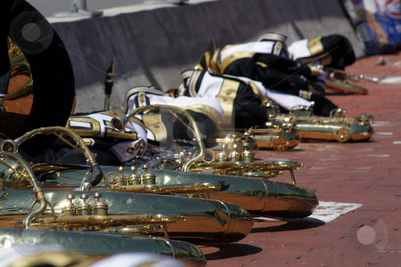 Marching Band Instruments stock photo, Marching band horn instruments, neatly placed on a brick pavement along with the uniform jackets. by Carl Stewart