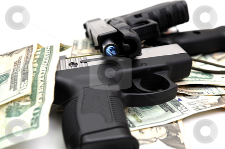 Handguns And Cash stock photo, Two semi automatic handguns on a pile of United States twenty dollar bills. The rifling of the pistol barrel is visible. by Lynn Bendickson