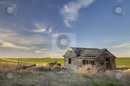 Abandoned homestead on prairie stock photo, Old abandoned house and farming machinery on Colorado prairie with green fields in background by Marek Uliasz