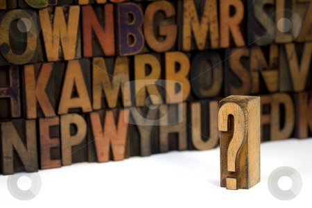 Question concept stock photo, Question mark against out of focus alphabet wall background - vintage letterpress wooden type stained by ink by Marek Uliasz