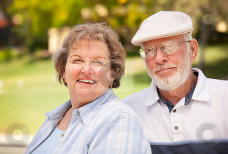 Happy Senior Couple in The Park stock photo, Happy Senior Couple Enjoying Each Other in The Park. by Andy Dean